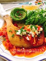 骨付き鶏もも肉のトマト煮込みチーズ添えの写真